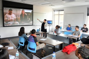 Photograph of Alison Lukowski teaching a first year composition class. She points to a screen with a video playing while students look on.